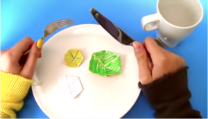 Hands holding knife over plate of hexaflexagons