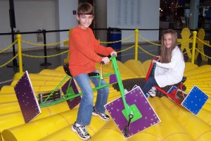 A boy and a girl riding square-wheeled tricycles at the Math Midway's Petal on Pedals activity.