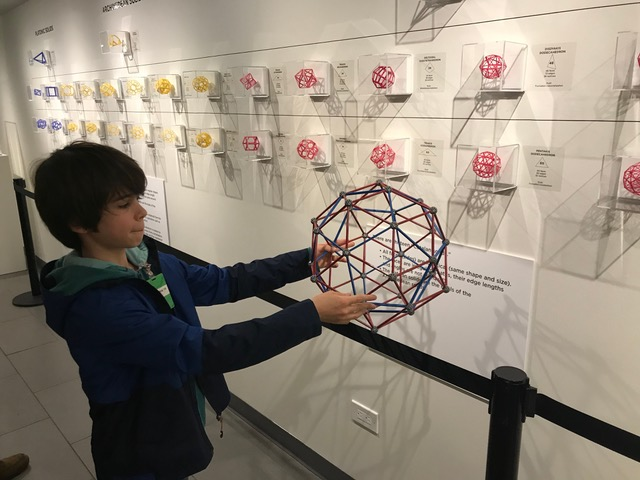 Side view of boy holding polyhedron