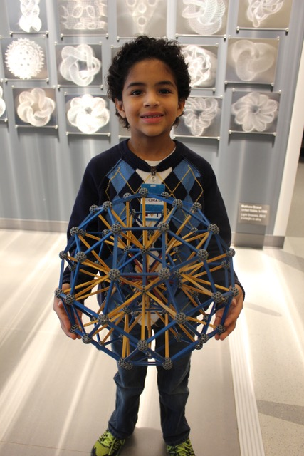 Front view of boy holding polyhedron