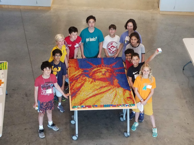 Children standing around Rubik's cube mosaic of the Statue of Liberty