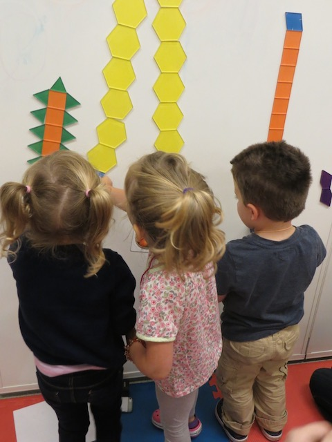 Children playing with tessellation tiles on white board