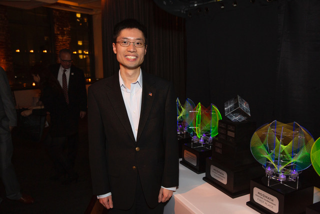 Po-Shen Loh standing next to trophies