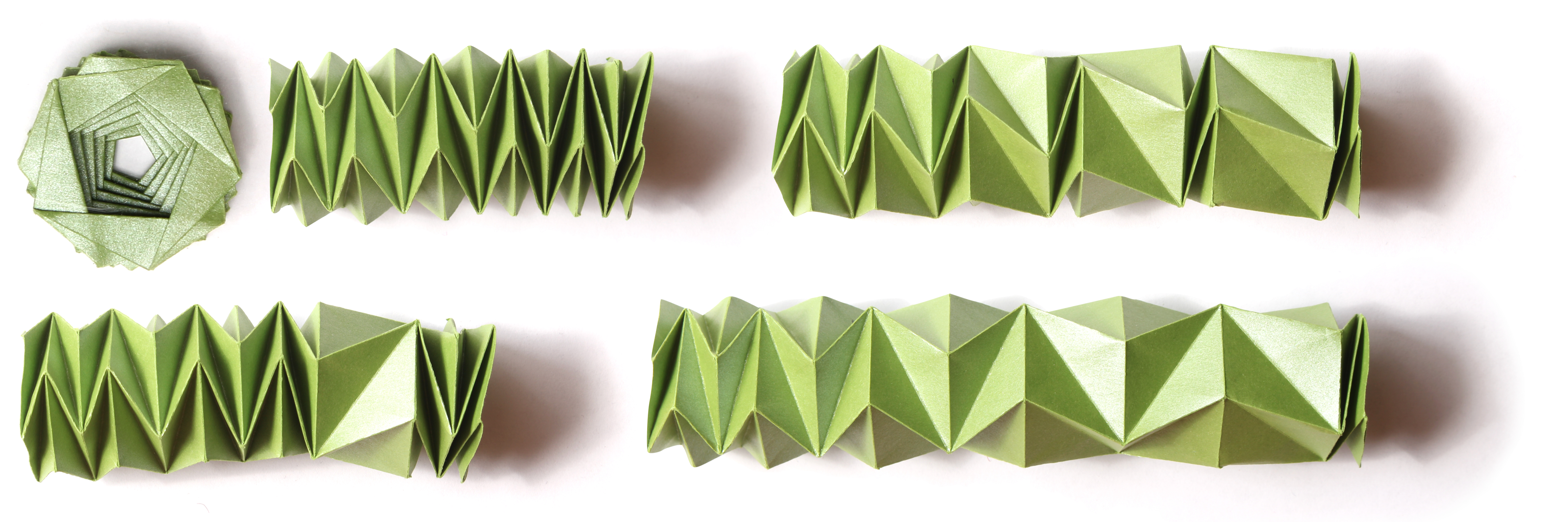 Three women wearing origami fashions