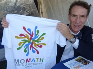 Bill Nye showing off a MoMath T-shirt (available at momath.org/shop).